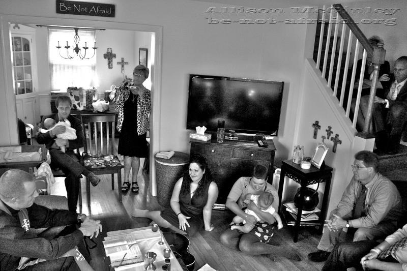 Family celebrating mass in living room